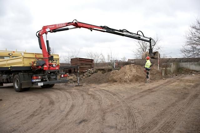Der heckmontierte Ladekran ist typisch für Lkw-Baufahrzeuge in Berlin. Ausgestattet mit Funksteuerung und 2Schalengreifer kann er auch Schüttgüter selber laden.