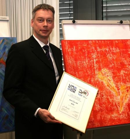 Oliver Racine, Leiter Internationales Produkt Management Einrichtungen, sichtlich erfreut über die begehrte Urkunde.