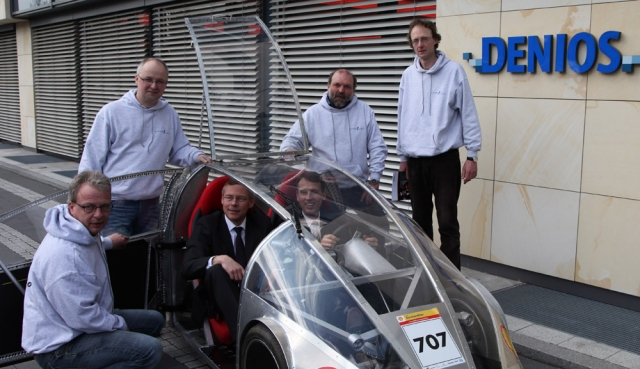 Auto News | Jörn Kortemeyer, Falko Marien, Uwe Klepzig und Peter Kröger (v. l. am Auto) vom Leo-Sympher-Berufskolleg präsentieren Harald Schule und Stefan Albrink (im Auto sitzend) von der DENIOS AG das Energiesparfahrzeug