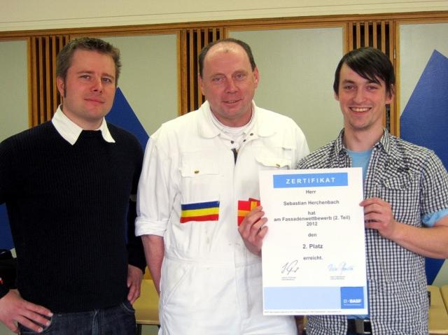Haussanierung: | Timo Späthling (Bauberater BASF Wall Systems) und Peter Schmidt (FL Bereich Farbtechnik BS Hof) beglückwünschen Sebastian Herchenbach zum zweiten Platz.