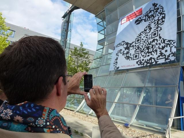 Auto News | Spaziergänger scannt auf dem Expo-Gelände einen QR-Code im Niedersachsenross