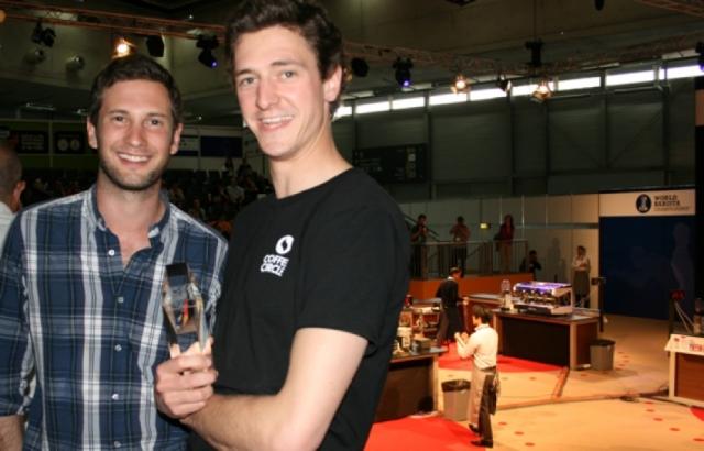 BIO @ Bio-News-Net | Moritz Waldstein-Wartenberg und Martin Elwert (v.l.) von Coffee Circle mit dem SCAE Award 2012 – im Hintergrund die World Barista Championship 2012 in Wien