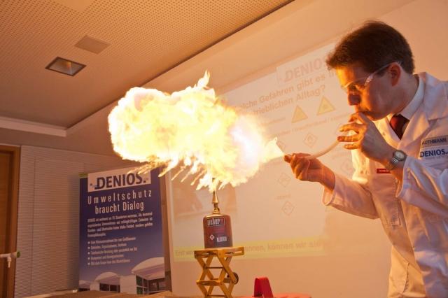 Versicherungen News & Infos | Tobias Authmann von der DENIOS AG weist mit dem Experimentalvortrag die Teilnehmer der DENIOS-Gefahrstofftage auf die Risiken im Umgang mit gefährlichen Stoffen hin.