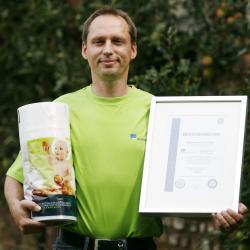 Alternative & Erneuerbare Energien News: Foto: Biofolien-Projektleiter Stephan Wilkens präsentiert die neue mit CO2-neutralem Strom produzierte Biofolie des Langerweher Folienherstellers alesco. In der anderen Hand hält er außerdem das Ökostrom-Zertifikat.