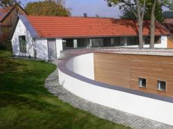 Fertighaus, Plusenergiehaus @ Hausbau-Seite.de | Foto: Passivhaus in Essenbach: Die ehemalige Hofstelle liegt an einem Hang und wird teilweise von einer im Bogen verlaufenden Mauer umfasst. Foto: Leipfinger-Bader.