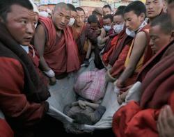Ost Nachrichten & Osten News | Foto: Mönche wickeln eine Tote in eine Decke.