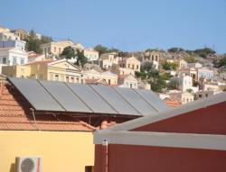 Alternative & Erneuerbare Energien News: Foto: Blick auf die malerische Hafenstadt Symi, im Vordergrund TiSUN Modulkollektoren.